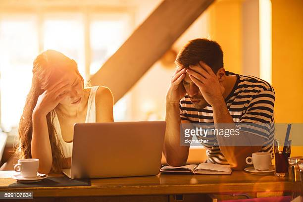 Young worried couple going through their home finances.