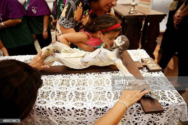 A young worshiper kisses a statue of Christ hanging on the cross in the Igreja Matriz da Nossa Senhora dos Remedios church during Semana Santa...