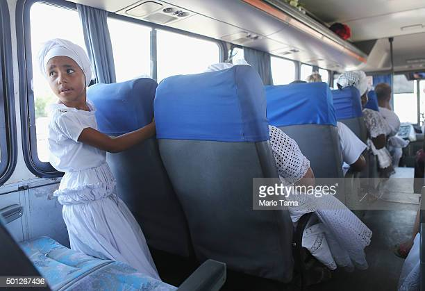 A young worshipper takes a bus to a beach on Guanabara Bay during a Candomble ceremony honoring goddesses Iemanja and Oxum on December 13 2015 in Sao...