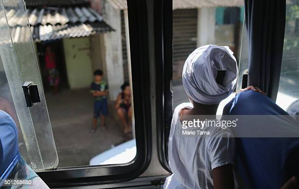 A young worshipper takes a bus to a beach on Guanabara Bay during a Candomble ceremony honoring goddesses Iemanja and Oxum on December 13 2015 in...