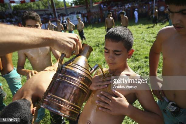 A young wrestler is seen as he is being smeared olive oil over his body before the competition during the 656th annual Kirkpinar Oil Wrestling...