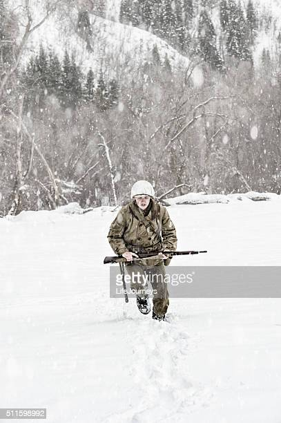 Young WWII US Soldier Crossing An Open Snowy Field