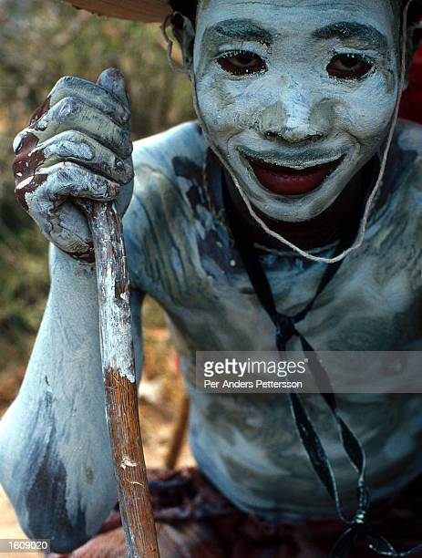 A young Xhosa boy holds a walking stick while smeared in gray clay as part of a manhood initiation rite July 11 2001 in Mdantsane outside East London...