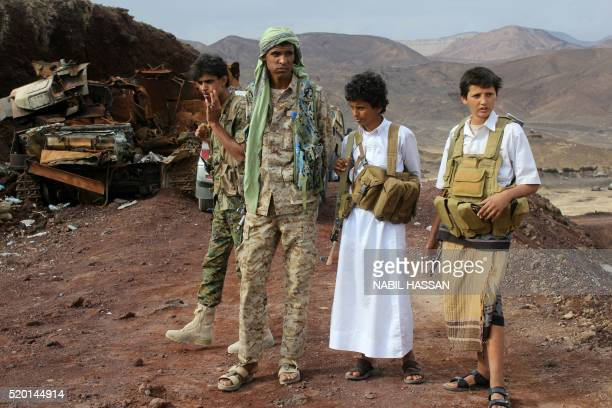 Young Yemeni fighters loyal to exiled President Abedrabbo Mansour Hadi stand next to a burnt tank in the Sirwah area in Marib province on April 9...