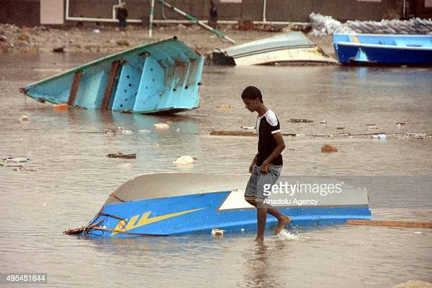 A young Yemeni walks through wind and heavy raincaused floodwaters as a result of Cyclone Chapala generated in the Arabian Sea on the shore of...