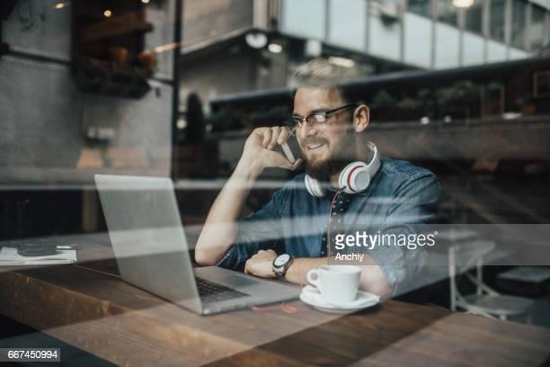Young Yuccie CEO im Gespräch mit Assistent am Telefon aus Café während der Kaffeepause