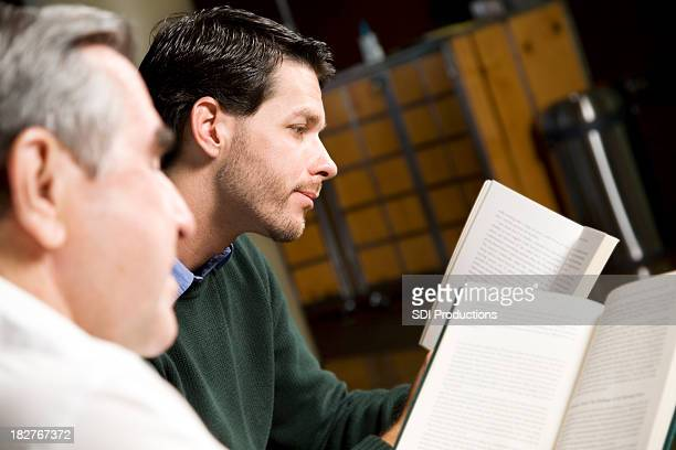 Younger and Older Man Reading Together