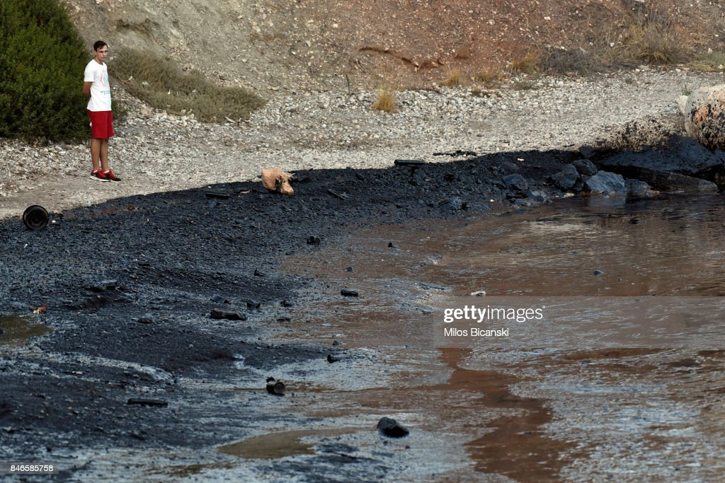 A youngh man inspects a beach on the coast of Salamis Island which has been polluted with oil on September 13, 2017 in Salamis, Greece. The small tanker 'Agia Zoni II' sank on September 10, whilst anchored off the coast of Salamis, near Greece's main port of Piraeus. It was carrying a cargo of 2,200 tons of fuel oil and 370 tons of marine gas oil. Salamis Island has suffered heavy pollution as a result in what has been called a 'major environmental disaster' by officials.