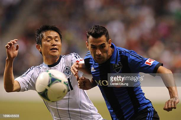 YoungPyo Lee of the Vancouver Whitecaps chases for the ball against Andres Romero of the Montreal Impact during the finals of the Amway Canadian...