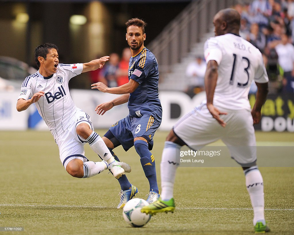 YoungPyo Lee of the Vancouver Whitecaps gets pushed off his feet by Marcelo Sarvas of the Los Angeles Galaxy while Nigel ReoCoker controls the ball...