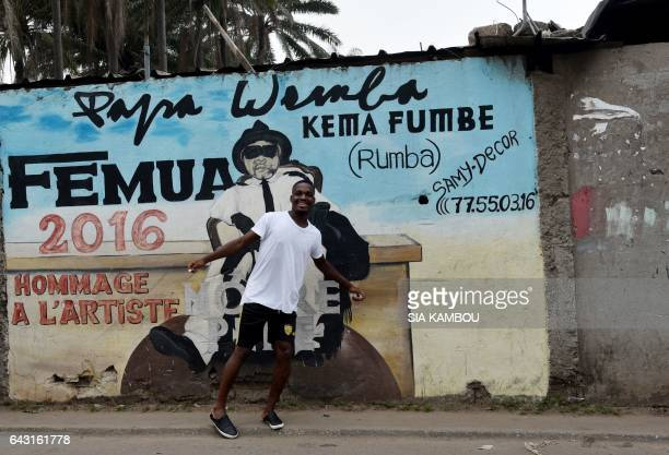 A youngster gestures next to a mural in tribute to Congolese rumba star Papa Wemba on February 20 2017 at Anoumabo district of Abidjan The flamboyant...