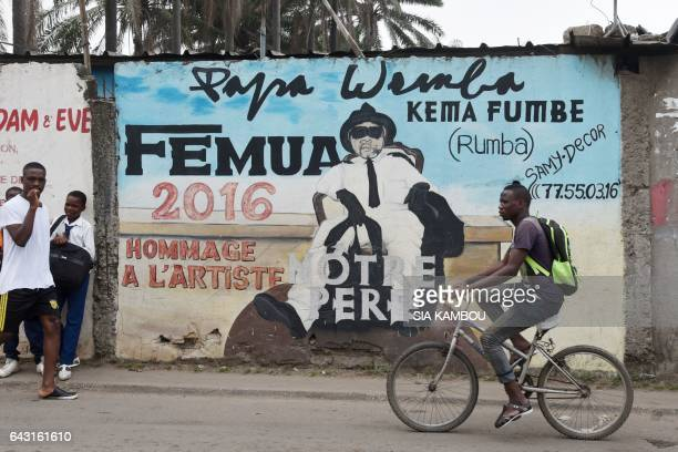 A youngster rides bicyle next to a mural in tribute to Congolese rumba star Papa Wemba on February 20 2017 at Anoumabo district of Abidjan The...