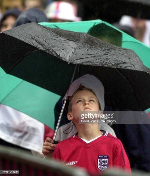 A youngster shelters from the rain as he watches the World Cup match between England and Argentina on a large open air screen in Birmingham Friday...