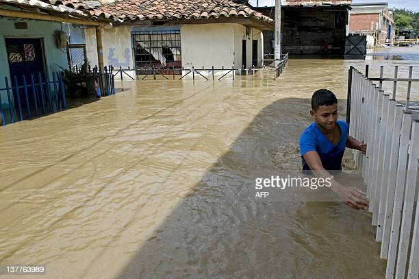 A youngster wades through a flooded street following the overflowing of the Cauca river on January 25 2012 in Candelaria department of Valle del...