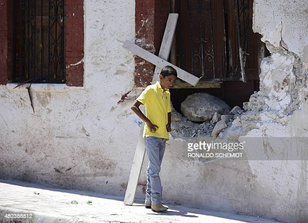 A youngster walks on July 30 in the site where a truck plowed into a crowd of pilgrims on the eve after apparently losing its brakes in Mazapil...