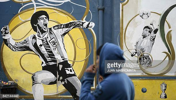 A youngster watches a graffiti depicting Argentine former football star Diego Maradona celebrating a goal and when scoring his famous 'hand of God'...