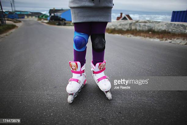 A youngster wears barbie doll rollerblades as she skates on the street on July 18 2013 in Ilulissat Greenland As Greenlanders adapt to the changing...