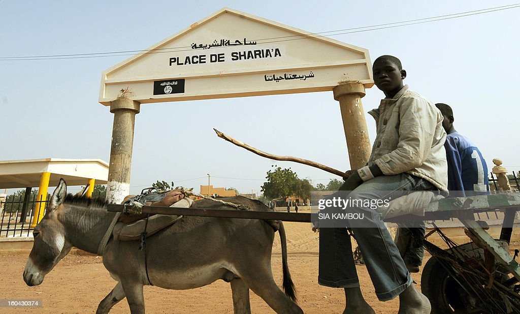 Youngsters are pictured past the entrance of Sharia Plaza on January 31, 2013 in the northern Malian city of Gao, where Islamists of the Movement for Oneness and Jihad in West Africa (MUJAO), who controlled the city, applied Islamic sharia law with public punishments, including stoning and amputation of limbs. Gao was retaken on January 26 by French and Malian troops in a major boost to the French-led offensive against the Al Qaeda-linked rebels, who have been holding Mali's vast desert north since last April. FP