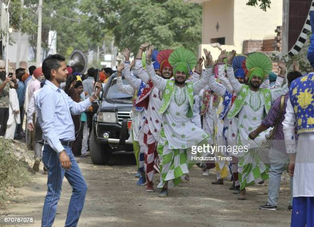 Youngsters of village college performing bhangra in front of cavalcade of Canadian Defence Minister Harjit Singh Sajjan to welcome during his visit...