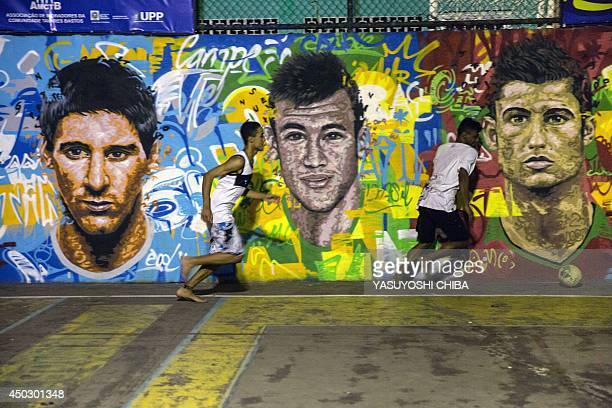 Youngsters play football in front of a mural of Argentine football player Lionel Messi Brazil's player Neymar da Silva Santos Junior and Portugal's...