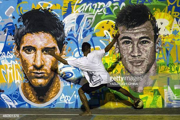 Youngsters play football in front of a mural of Argentine football player Lionel Messi and Brazil's player Neymar da Silva Santos Junior at a field...