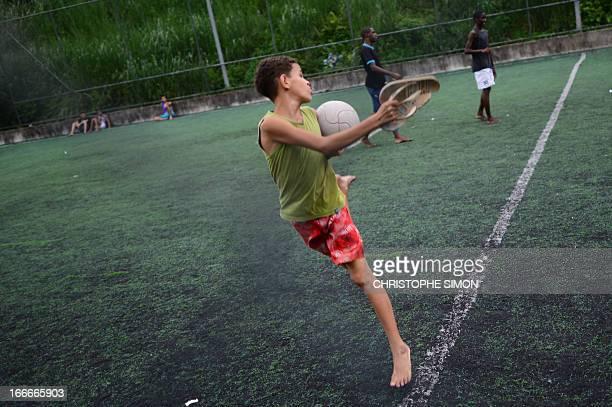 Youngsters play football on a field in the Cidade de Deus shantytown Rio de Janeiro Brazil on April 13 2013 AFP PHOTO/CHRISTOPHE SIMON