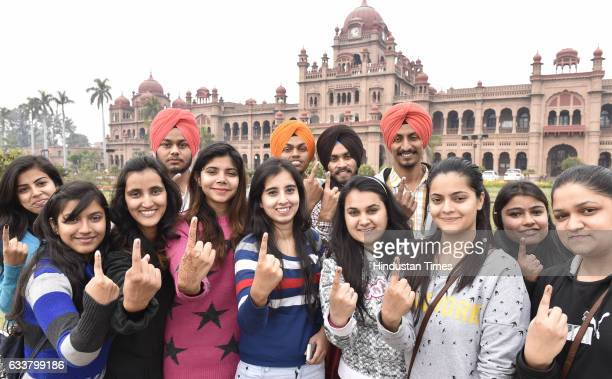 Youngsters show their inked fingers after voting near the polling station on February 4 2017 in Amritsar India Punjab on Saturday voted in its first...