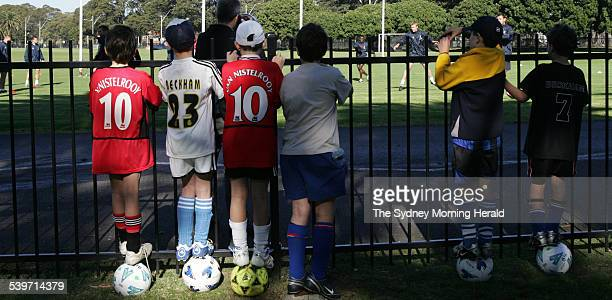 Youngsters taking part in a football camp at Moore Park take time out to look over the fence to watch Dwight Yorke taking part in his first training...
