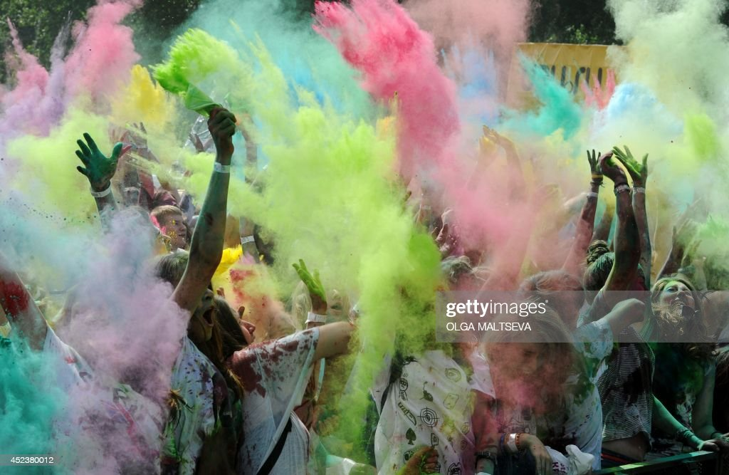Youngsters throw colored powder at each other during the Festival of Colors in St. Petersburg on July 19, 2014. The feastival is based on the Indian festival Holi.