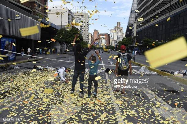 TOPSHOT Youngsters throw on the avenue unused subway tickets during an antigovernment protest in Caracas on July 20 2017 A 24hour nationwide strike...
