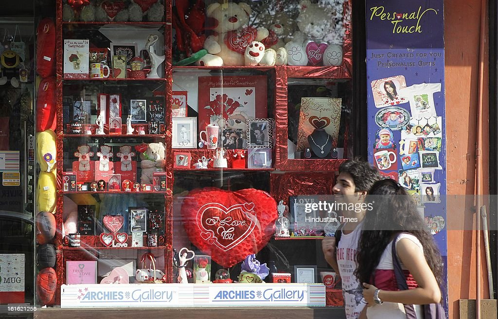 Youngsters walk past the gift articles displayed at a store window for sale, day ahead of Valentine's Day at Churchgate on February 13, 2013 in Mumbai, India.