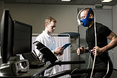 Athlete in oxygen mask running on treadmill and medic in white uniform