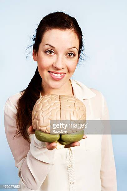 Your thinking apparatus! Pretty brunette holds out model brain