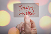 You`re invited card in hand with blurred bokeh lights in the background