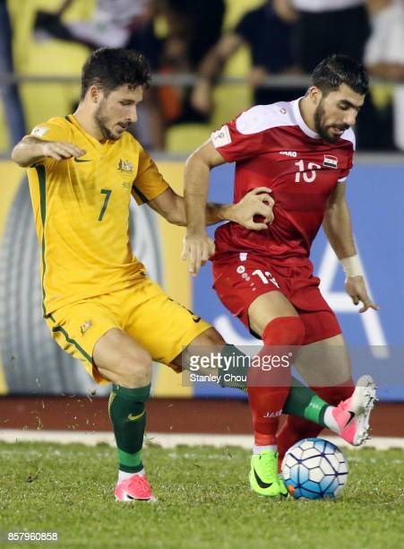 Yousef Kalfa of Syria holds off Mathew Leckie of Australia during the 2018 FIFA World Cup Asian Playoff match between Syria and the Australia...
