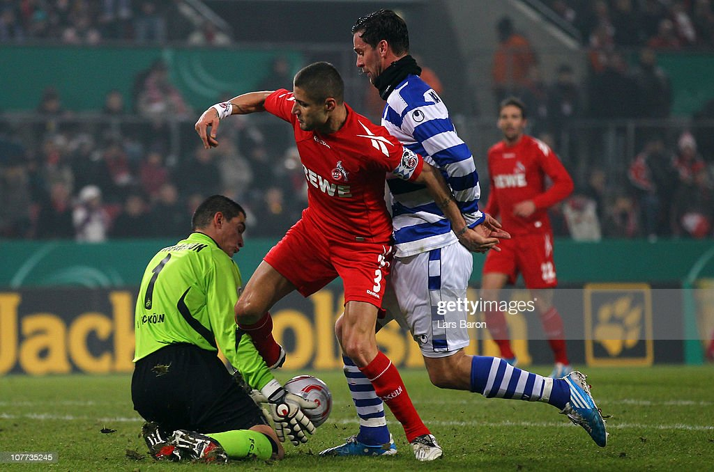 Youssef Mohamad and goalkeeper Faryd Mondragon of Koeln are challenged by Stefan Maierhofer of Duisburg during the DFB Cup round of sixteen match between 1. FC Koeln and MSV Duisburg at RheinEnergie Stadium on December 22, 2010 in Cologne, Germany.