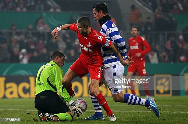 Youssef Mohamad and goalkeeper Faryd Mondragon of Koeln are challenged by Stefan Maierhofer of Duisburg during the DFB Cup round of sixteen match...