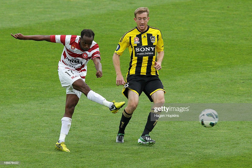 Youssouf Hersi of the Wanderers takes a shot at goal while Alexander Smith of the Phoenix looks on during the round 16 A-League match between the Wellington Phoenix and the Western Sydney Wanderers at Westpac Stadium on January 13, 2013 in Wellington, New Zealand.