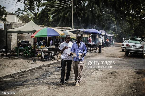 A youth activist distributes leaflets on the UReport at a food market on November 29 2014 in Lusaka The UReport is a youthcentered program created by...