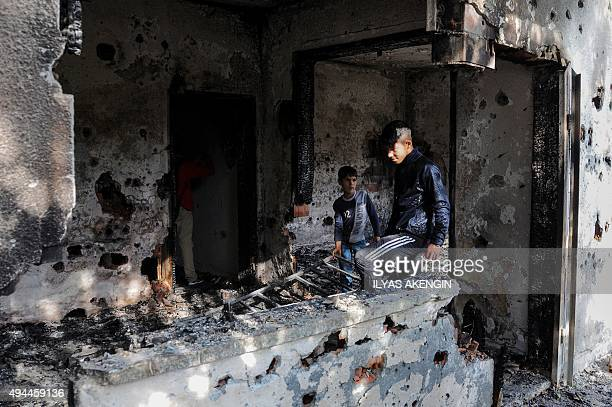 A youth and a boy walk inside a burnt and bulletriddled house following clashes between Islamic State group fighters and Turkish special forces in...