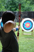 Youth boy taking aim at an archery target