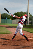 Little league baseball player at the plate, swinging the baseball bat from behind.