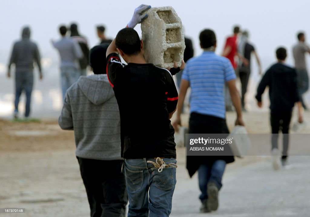 Youth carry breeze blocks as they walk towards the scene of clashes between Palestinian stone throwers and Israeli soldiers close to the Israeli Ofer military prison, near the West Bank village of Betunia, on November 8, 2013. The clashes errupted a day after Israeli forces killed a Palestinian near Jerusalem, Israeli police and family members said, as the United States warned of a third intifada if Middle East peace talks fail. AFP PHOTO/ABBAS MOMANI