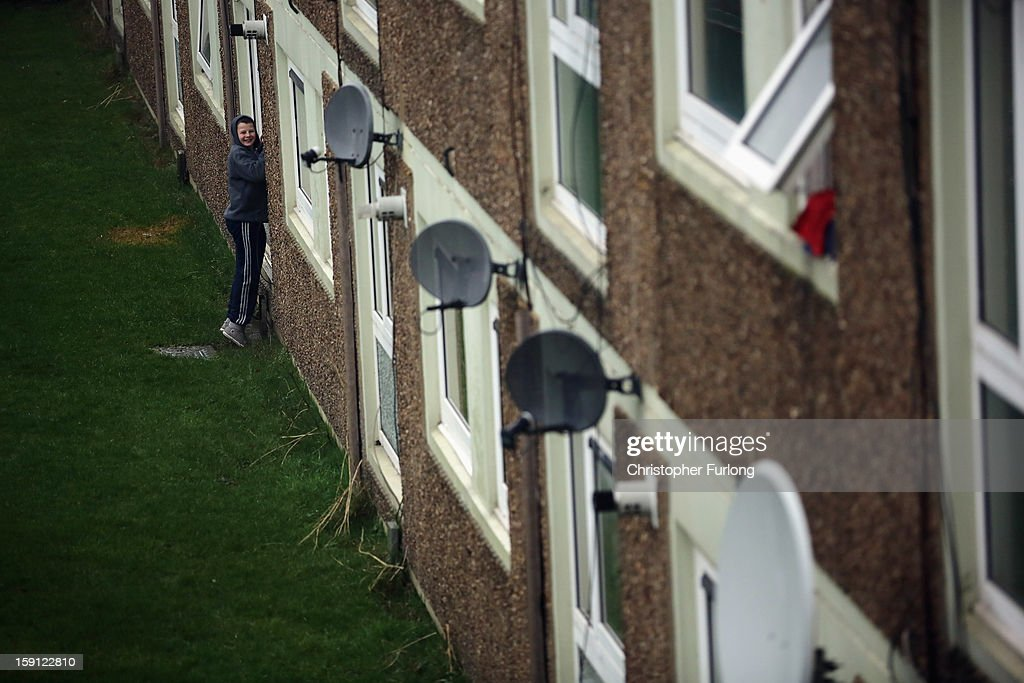 A youth chats to a friend through a window on he Falinge Estate, which has been surveyed as the most deprived area in England for a fifth year in a row, on January 8, 2013 in Rochdale, England. According to data provided by the Department for Communities and Local Government, 72 per cent of people in the local area are unemployed and seven per cent have never had a job. Four out of five children on the estate are living in poverty, with the area having one of the highest teenage pregnancy rates in the country. During today's House of Commons debate, the government urged MPs to back their planned 1 per cent cap on annual rises in benefits and some tax credits for three years from next April. Benefits for people of working age have historically risen in line with the rate of inflation.