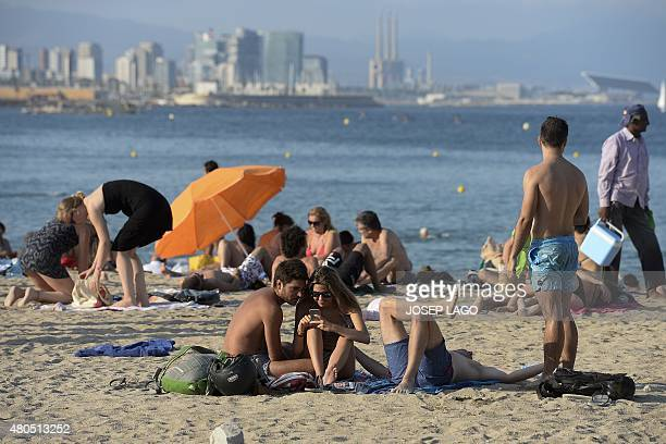 Youth check a mobile phone on a beach of Barcelona on July 12 2015 AFP PHOTO/ JOSEP LAGO