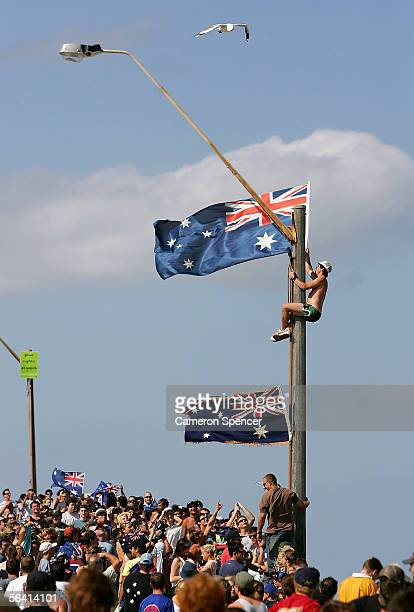A youth climbs a telegraph pole and erects an Australian flag during unrest at Cronulla beach December 11 2005 in Cronulla Australia Angry crowds...