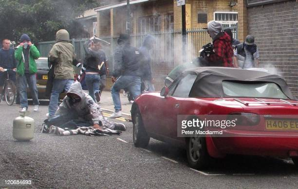 A youth collects clothing looted from a Carhartt store in Hackney as a car smoulders on August 8 2011 in London England Pockets of rioting and...