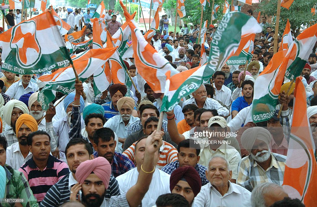 Youth Congress activists wave flags as they protest against state government for recent rises in electricity tariffs during a demonstration in Amritsar on April 21, 2013. Power consumers in Punjab may have to shell out more on consuming energy as state's sector regulator Punjab State Electricity Regulatory Commission (PSERC) is set to announce a hike in tariffs for the financial year 2013-14.