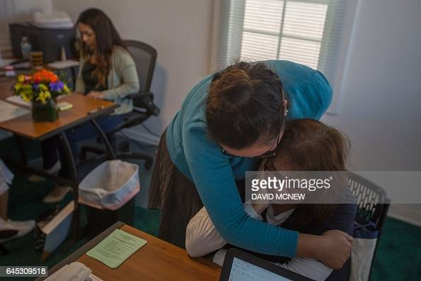 Youth coordinator Samantha Yanez comforts Gloria Eliza as she cries while applying for citizenship at the TODEC office on February 24 2017 in...