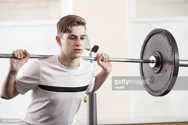 youth engaged in sports exercises with a barbell.